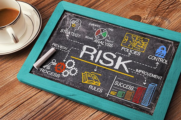 chalkboard on desk with the word risk on it