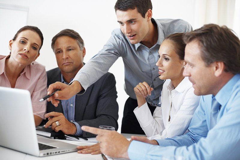 Business professionals gathered around a laptop