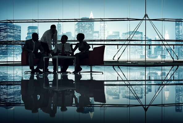 four people gathered around a conference table